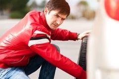 Änderndes Reifenrad des männlichen Fahrers nach Zusammenbruch stockfotos