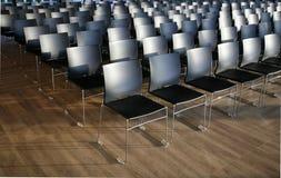 Ändlösa rader av stolar i en modern konferenskorridor Arkivbilder
