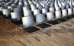 Ändlösa rader av stolar i en modern konferenskorridor Arkivfoton