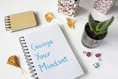 Ändra din mindset som är skriftlig i anteckningsbok arkivbild