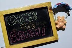 ÄNDRA SYSTEMET! på färgrikt handskrivet för uttryck på svart tavla royaltyfri fotografi