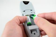 Ändrande batterier i en fjärrkontroll Royaltyfri Foto