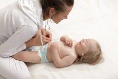 Ändrande blöja för mamma till behandla som ett barn som ligger på hans baksida royaltyfri foto