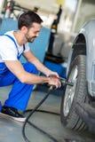 Ändrande däck för auto mekaniker på bilen Royaltyfria Bilder