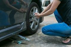 Ändrande däck för kvinnlig chaufför på hennes brutna bil Arkivfoton