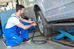 Ändrande däck för mekaniker på bilen med luftskiftnyckeln Fotografering för Bildbyråer