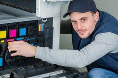 Ändrande färgpulverkassetter för man i fotokopiator Arkivfoton