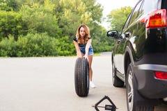 Ändrande gummihjul för kvinna på en väg Arkivbild