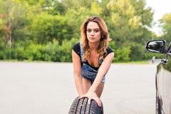 Ändrande gummihjul för kvinna på en väg Royaltyfria Foton