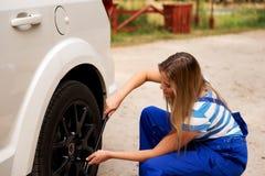 Ändrande gummihjul för kvinnlig mekaniker med hjulskiftnyckeln Royaltyfri Bild