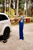 Ändrande gummihjul för kvinnlig mekaniker med hjulskiftnyckeln Royaltyfria Bilder