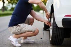 Ändrande gummihjul för man med hjulskiftnyckeln på den brutna bilen Royaltyfri Fotografi