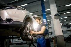 Ändrande gummihjul för mekaniker med det manuella hjälpmedlet i epairgarage Fotografering för Bildbyråer