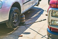 Ändrande hjul eller gummihjul på en grå bil på en utomhus- bilservice med den gamla stålar royaltyfri bild
