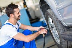 Ändrande hjul för mekaniker på bilen arkivfoto