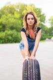 Ändrande hjul för sexig kvinna på en vägren Arkivfoton