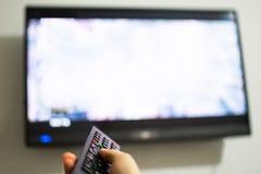 Ändrande kanaler för manhand på TV:N Royaltyfria Bilder