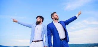 ändrande kurs Formella dräktchefer för män som pekar på motsatta riktningar Nya affärsriktningar Framkallande affär arkivbild