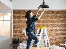 Ändrande lightbulb för kvinna i hennes rum Royaltyfri Fotografi