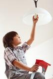 Ändrande lightbulb för pojke Fotografering för Bildbyråer