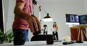 Ändrande lins för manlig fotograf av kameran 4k arkivfilmer