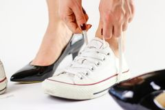 Ändrande skor för flicka Tar bort svarta skor och bär den vita gymnastikskon Royaltyfria Foton