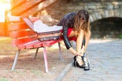 Ändrande skor för kvinna på en bänk Arkivbilder