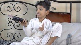 Ändrande TV-kanal för gulligt indiskt asiatiskt caucasian pojkebarn med avlägset och att försöka för att göra den att arbeta, gen