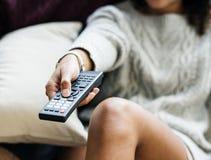 Ändrande TV-kanal för kvinna med den avlägsna kontrollanten royaltyfri fotografi