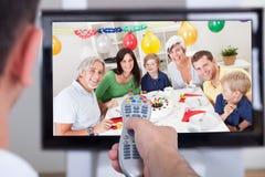 Ändrande TV-kanal för man till och med fjärrkontrollen royaltyfri bild