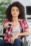 Ändrande TV-station för härlig brunett i vardagsrum Royaltyfri Foto