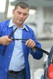 Ändrande vindrutetorkareblad för mekaniker på bilen Fotografering för Bildbyråer