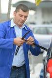 Ändrande vindrutetorkareblad för mekaniker på bilen Royaltyfri Foto