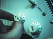 Ändrande volym för man på den elektroniska gitarren royaltyfri fotografi