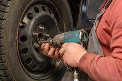 Ändring av hjulet med en inverkanchaufför royaltyfri foto