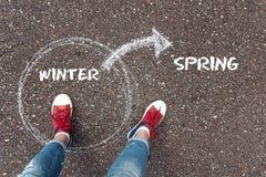 Ändring av vintern som fjädrar Fot i röda gymnastikskor som står på asfalten royaltyfria bilder