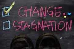 Ändring eller inaktivitet som är skriftliga med färgkritabegrepp på svart tavla royaltyfria bilder