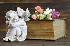 Ängel, blommor och gammal bok Arkivfoton