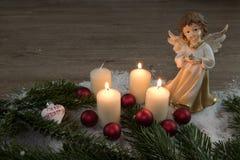 Ängel med bränningstearinljus i snön och de röda julbollarna Fotografering för Bildbyråer
