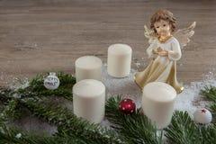 Ängel med stearinljus i snö och julbollarna Arkivbild