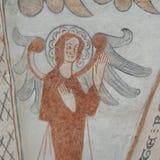 Ängel med två stora vingar som lyfter upp hans händer, en gotisk freskomålning Arkivbild