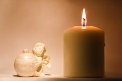 Ängel och stearinljus i lilor Arkivfoton