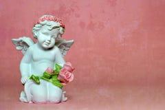 Ängel som knäfaller och rymmer blommor Royaltyfri Fotografi