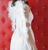 Ängelflickavingar på baksida i den vita klänningen på röd bakgrund royaltyfri fotografi
