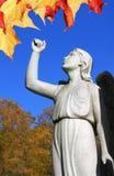 Ängelstaty i kyrkogård med den lyftta armen och sidor royaltyfria foton