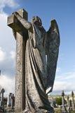 Ängelstaty som omfamnar ett kors och en celtic kyrkogård Royaltyfri Foto