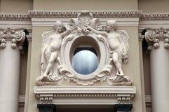 Ängelstatyer och ovalt fönster på den barocka stilfasaden arkivbilder