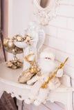 Ängelstatyett med guld- julprydnader och sidor i bunke och liten vit jultomten som sitter på dressingtabellen Arkivfoton