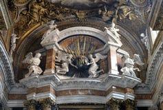 Änglar som rymmer ett jordklot med guld- strålar och initialer IMAS för namnen Jesus och Maria Royaltyfri Foto