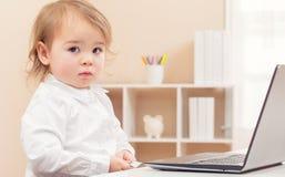 Ängslig litet barnflicka som använder en bärbar dator royaltyfri bild